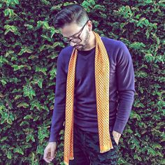 Casual and cool in a purple sweater and yellow silk scarf.