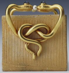 One of three match holders formed of bricks made by the Gusareva factory in Moscow and now in the Royal Collection, two of which are by Fabergé. This example by Fabergé is mounted with gold handles in the form of pairs of entwined serpents decorated with sapphires and pearls; workmaster Erik Kollin, before 1896. Acquired by King Edward VII, date unknown. (detail)