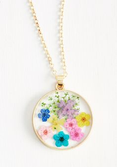 PROMO MARK: From the Blossom of My Heart Necklace. When feelings for your sweetie grow bright like the flowers pressed in this gold necklace's clear pendant, dont hold back. #multi #modcloth