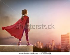 Little child girl plays superhero. Child on the background of sunset sky. Girl power concept - stock photo