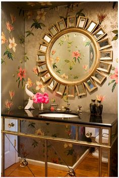 Mirrored console with floral wallpaper and sunburst mirror