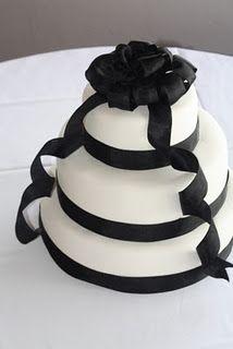 Elegant white wedding cake with black ribbon. BECCA'S blue BAKERY