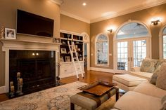 Traditional Living Room with Crown molding, Hardwood floors, Paisley Pillow, Wall sconce, Carpet, Built-in bookshelf