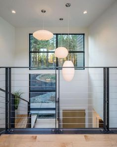 Top of Stairs Wire Railing View Featuring Layered Shaped Pendant Light Trio Over Double Height Ceiling Wood Railings For Stairs, Deck Railing Design, Wrought Iron Stair Railing, Oak Stairs, Metal Stairs, Railing Ideas, Hand Railing, Metal Balusters, Stair Design