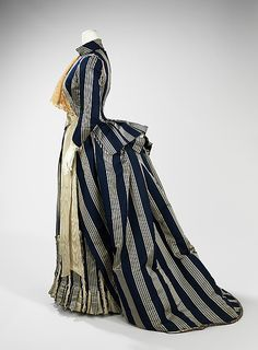 Haute Couture Charles Frederick Worth afternoon walking dress gown circa from French 1885. Made from silk with lace trimming marked by darker colors in stripe line asymmetrical drapery oversize accessories and elongated forms include the bustle skirt at the back. The dense textiles preferred were covered in trimming, beadwork, puffs and bows to visually elevate them further. #HauteCouture #Fashion House of Worth