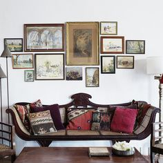 This globetrotting jeweller has collated treasures from her travels to create a colonial feel, fusing influences from France, India and Africa in her 100-year-old Goan home. Here, she has hung framed artwork to create a feature wall above this vintage Indian sofa<span>Photography: Anna Kern  Styling Eva Lindh/House of Pictures</span>