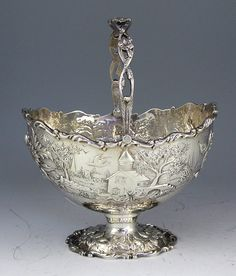 A Samuel Kirk sterling silver sugar basket with swing handle in the Landscape pattern with buildings and gardens chased into the oval shaped basket.  marked S. Kirk and Son Co and 925/1000 and sterling