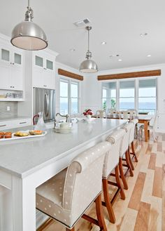 relaxing beach house kitchen. Like the wooden floor pattern, the polka dots beige chairs, the industrial hanging lights with all the white. The view is not bad either :)