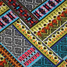 """Purple Blue Orange Tiki Ethnic Rows Cotton Spandex Knit Fabric - A lovely color palette of turquoise blue, orange, yellow, and purple tiki aztec inspired ethnic design on a white on a  top quality cotton spandex knit.  Fabric has a smooth and soft hand, and is mid weight with a 4 way stretch.  Pattern repeat measures 28"""".  ::  $6.75"""