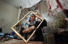 Palestinian woman Amal Abu-Rqayiq works at her small carpentry work-shop in the Nusseirat refugee camp in the Gaza City, Gaza on March 8, 2014. Amal is a 40-year-old divorcee and working in a male-dominated profession to help raise a daughter with special needs. (Ashraf Amra/Anadolu Agency/Getty Images)