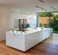 Huge kitchen bench...love the white against the wooden floors.  So clean.  And beautiful big floor to ceiling windows too.