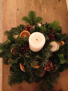 Homemade Christmas candle decoration with pine cones and dried fruit.