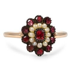 This majestic Georgian ring showcases a vivid cushion-shaped garnet encircled by twelve seed pearls and ten round garnet accents all set in sterling silver. The petite yellow gold band and divine floral design brings glamour and elegance to this classic ring (Garnet approx. 0.52 total carat weight).