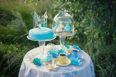 """By """"Cotton"""" Photography & Decor Studio http://www.cottonwedding.com/. cyan, blue, yellow pastel candy bar decorated with paper flowers. hand made sweets, paper decor, paper wall, sunset, love story on grass field"""