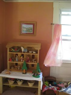 dollhouse on low table, with small baskets of supplies.  Trees and table cloth- image via Morning Glory Garden Handbook