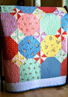 Colourful Octogon quilt- Nice! I like the snowball arrangement with pinwheels. Could replace the pinwheels with tiny pieced blocks of anything. Nice way to combine big bits of cool statement fabric with cute piecing too.