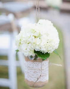Kaitlyn & Tim: Our aisle decor. Burlap, lace, and twine wrapped mason jars hanging from shepherd hooks. White hydrangea.