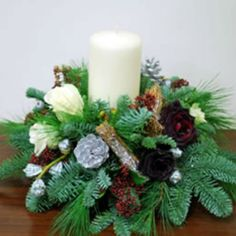 Christmas Table Centre on a foam base with an ivory pillar candle, dark red and white Roses, pine cones, cinnamon sticks, fresh pine and red berries. Part of Seasons 2017 Christmas Collection.