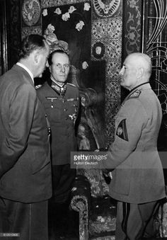 German Field Marshal Erwin Rommel,  (centre), talks to Benito Mussolini  and the German Ambassador to Italy Rahn  at a reception, Italy, 1943.