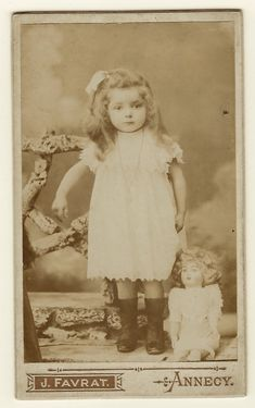 This carte de visite photograph features a portrait of an adorable little girl. She has the most interesting riveting eyes. She is wearing a long necklace and has a bow in her hair. The child is we…