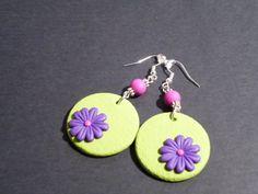 Orecchini trendy con margheritone viola su base verde.