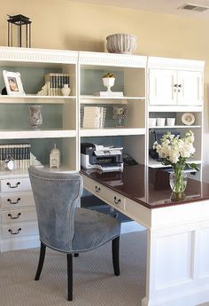 White bookshelves and a white desk in this office work well with a dark wood desktop. The blue grey suede chair is a nice, neutral choice of seating.