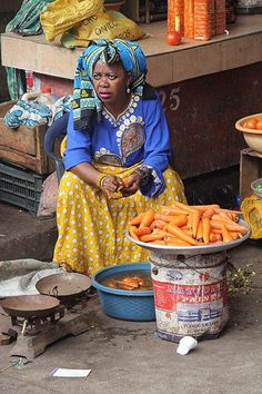 Market woman cleaning some carrots, Moroni, Comoros