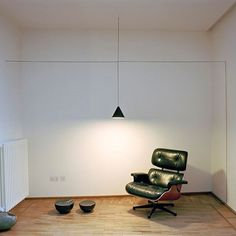 A Flos STRING LIGHT (Michael Anastassiades, 2014) illuminates a Herman Miller EAMES Lounge Chair (Charles + Ray Eames, 1956).