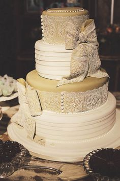 Bolo de casamento com quatro andares em tons de off white e areia com laços de rendas de açúcar. Sugar Veil Cake Por Casal Garcia Bolos, via blog Vestida de Noiva