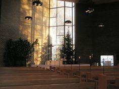 Kirkko sisältä. Huomaa kynttilät penkkien päissä. Jouluaika.