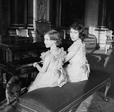 Princess Elizabeth and Princess Margaret sitting at the Piano in the Music Room of Buckingham Palace. On their feet is little Dookie, their corgi. December 20, 1938.