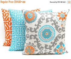 Set of three of decorative throw pillows in oh so pretty turquoise, orange and gray on a natural background. This fabric is an elegant