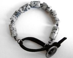 $24.99 The layers of black speckles in the this white quartz gives the stone a nice neutral gray appearance, but the addition of faux black suede in this design does tend to pull out some those larger black spots. The comfy, casual design of this bracelet and the go-with-everything colors makes this an easy piece to grab as you're running out the door.
