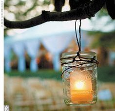 mason jars hanging on all trees for an evening outside wedding