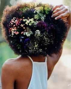 A woman is putting flowers in her hair to challenge how people see Afros.