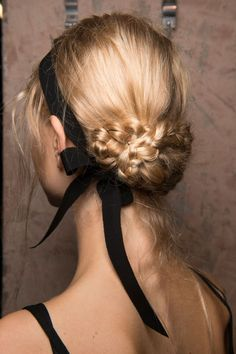 A black ribbon acts as both a headband and a decorative bow, framing the intricate braided bun at the Erdem spring 2017 show.
