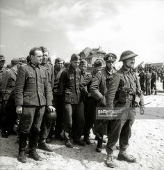 A Canadian soldier stands at the head of a group of German prisoners of war, including two officers, on Juno Beach at Bernières-sur-Mer, Normandy, France, June 1944. The German troops surrendered at Courseulles-sur-Mer, also on Juno beach, on D-Day, 6th June 1944. The house in the background is one of the first to be liberated by Canadian soldiers on D-Day and has been known since as La Maison des Canadiens.