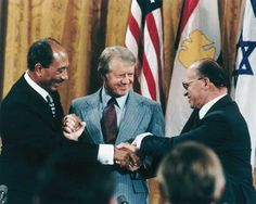 Egyptian President Anwar el-Sādāt (left), U.S. President Jimmy Carter, and Israeli Prime Minister Menachem Begin shaking hands at the White House after signing the Camp David Accords peace treaty between Israel and Egypt, September 17, 1978.
