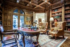 Providing for great entertaining flow, the entrance hall leads to the study. Capped by an ornately carved, cross-beamed ceiling, the richly paneled study is centered by a wood-burning fireplace, with a marble surround and a wood-carved mantle, and also features abundant built-in bookcases.