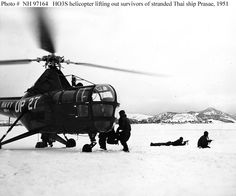 """""""Thorin, D.W., APC, prepares to take off in his helicopter with another load of survivors from the Thailand corvette, the HMTS Prasae, which ran aground during a blinding snow storm off the coast of Korea. Other members of the helicopters stand guard as the rescue was affected behind enemy lines.""""  Photo is dated 16 January 1951, but was taken several days earlier. Helicopter is a Sikorsky HO3S-1 of squadron HU-1."""