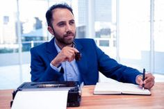 Thoughtful businessman holding pen while sitting at desk Royalty Free Stock Images