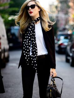 Editor Joanna Hillman wears a basic white t-shirt with layered necklaces, a polka dot skinny scarf, and belted black jeans
