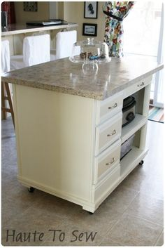 Small kitchen island on wheels, have butcher block or dark wood top.
