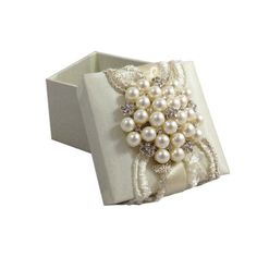 This silk covered wedding favor box is a timeless piece of art. Hand-crafted in Thailand, embellished with a large pearl brooch, attached to imported embroidered lace fabric from Indonesia. Fill them with candy, truffles or little gift ornaments, such favor boxes will be remembered for long. Now featured on DennisWisser.com at discounted wholesale price.