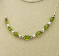 https://dianakirkpatrick.com/product/peridot-pearl-silver-necklace/  An original necklace design for the bride - peridot nuggets with white freshwater pearls and antiqued sterling silver beads.  Magnetic clasp.  www.dianakirkpatrick.com