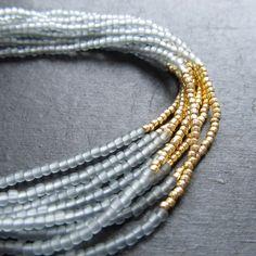 Náramek+korálky+šedé+a+zlato+Náramek+hodící+se+k+obšívaným+náušnicím+se+zlatým+kaplíkem.+Materiál:+matný+toho+rokajl,+zlatý+toho+rokajl,navlékací+nit,bižuterní+americké+zapínání++Rozměr:+délka18,5+cm,+možno+prodloužit+kroužkyu+zapínání++