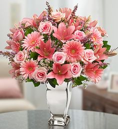 Add an elegant glow to her day. With the shimmering silvered vase and the posh pink arrangement of this truly original gift, there's no doubt she'll rise to celebrity status in no time. Stunning fresh roses, lilies, carnations and more bring eye-catching beauty and stylish sophistication to any setting.
