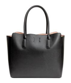 Black. Shopper in supple faux leather with two handles and a magnetic fastener at top. Unlined. Size 6 3/4 x 11 x 12 3/4 in.
