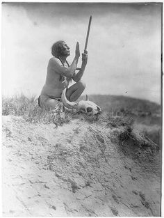 Slow Bull, squatting, wearing breechcloth, holding pipe with mouthpiece pointing skyward, buffalo skull at his feet.