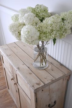 love this from Frugal Farmhouse Designs.... fresh flowers, white hydrangeas no less, lovely weathered natural wood, simple bead boarding  a couple of oars, my kind of chic, nautical and coastal